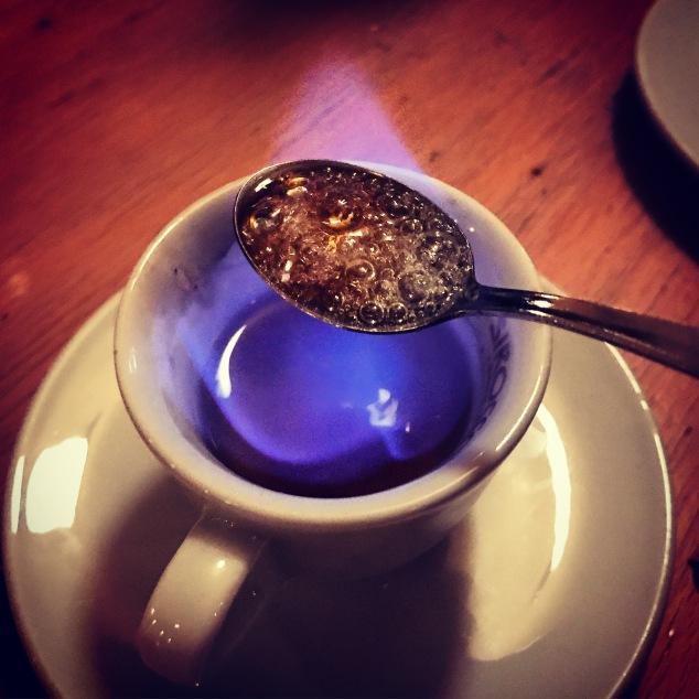 Zucker wird über dem brennenden Alkohol in einer Tasse geschmolzen.