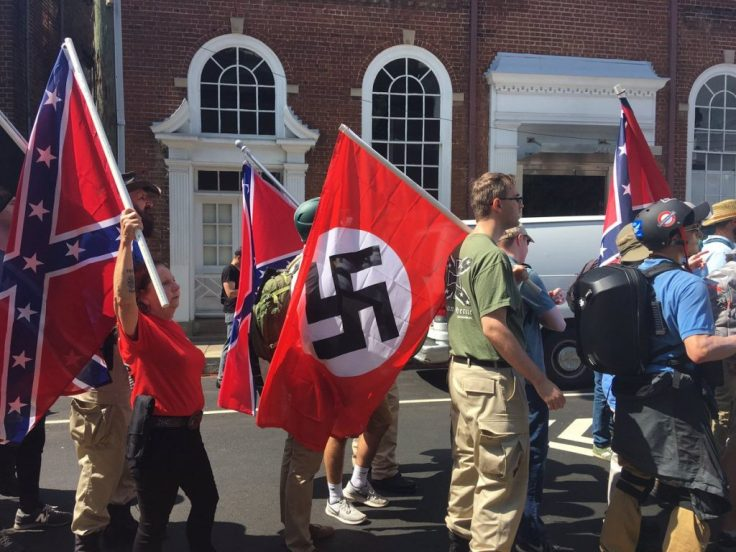 white people carrying flags of the Confederacy, and of Nazi Germany.