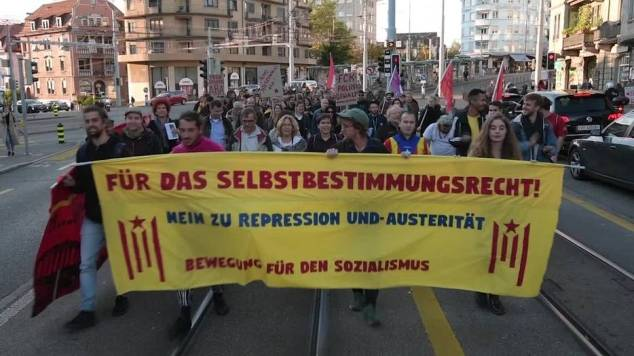 Bild von marschierenden Menschen mit einem Transparent: für das Selbstbestimmungsrecht.