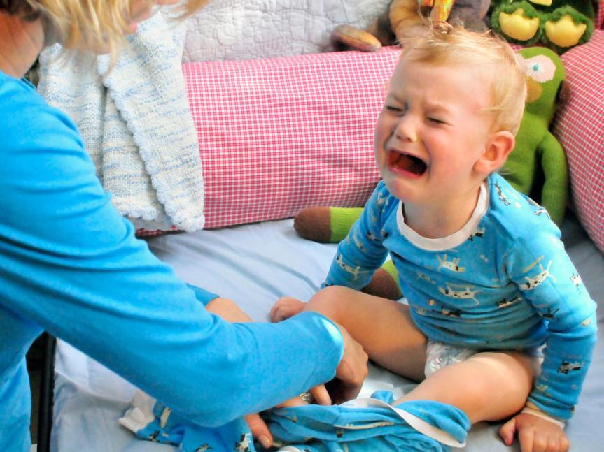 Kind das weint, weil es Kleider anziehen muss.