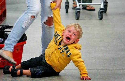 Kind, das im Supermarkt schreiend am Boden liegt.