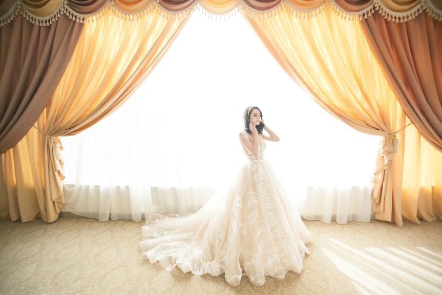Frau in Hochzeitskleid vor grossem Fenster mit opulenten Vorhängen
