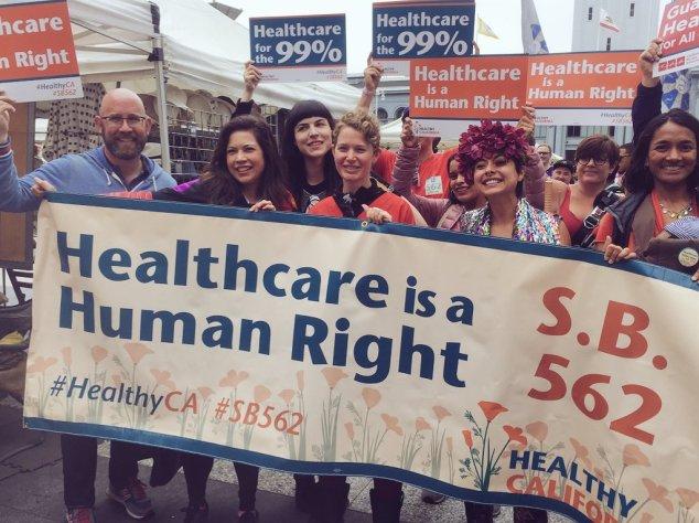 Demonstranten mit einem Transparent auf dem steht, dass die Krankenversorgung ein Menschenrecht ist.