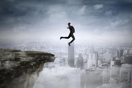 eine Frau im Anzug springt von einer Klippe über einer Grossstadt.