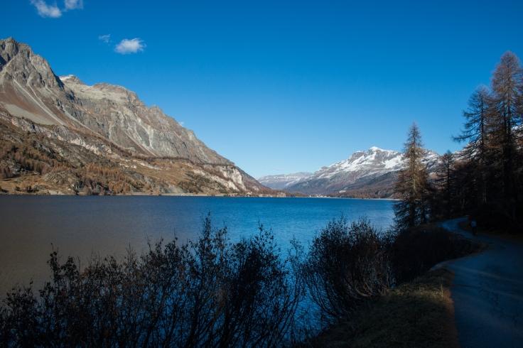 Landschaftsbild mit einem See und Bergen im Hintergrund.